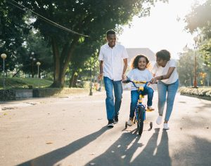Mom and dad with a child on a bike in a park