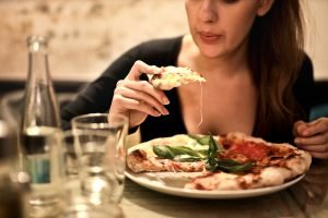 A woman eating a pizza in a restaurant