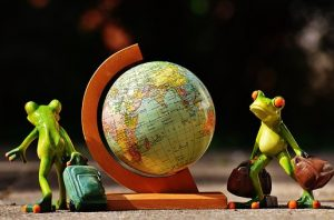 two frogs carrying bags around the globe model