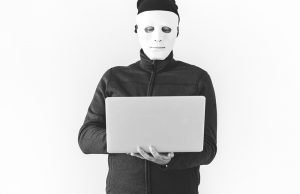 A man with a white mask, holding a laptop