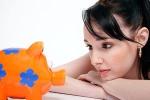 girl looking at a piggy bank