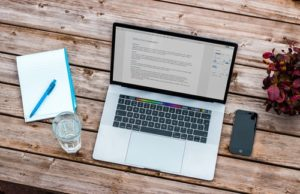 a laptop, notebook, cell phone and a glass of water on the table
